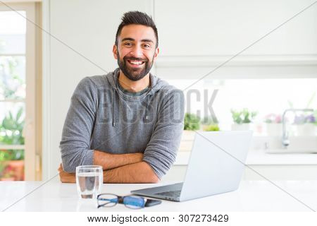 Handsome hispanic man working using computer laptop happy face smiling with crossed arms looking at the camera. Positive person.