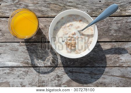 Outdoors Breakfast With Orange Juice And A Bowl Of Cereals And Milk On A Wooden Table In Sunlight To