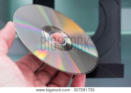 Man Hand Holding A Cd Above A Cd Player Close-up View