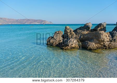 Vacationers Enjoy Warm Shallow Waters On A Coast Of Crete Island In Greece.