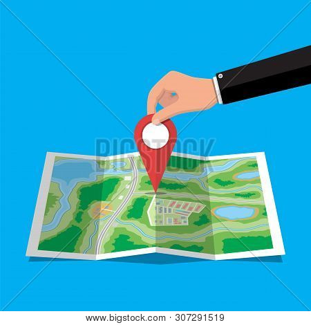 Location Pin In Hand And Paper Map. City Map With Houses, Parks, Streets And Roads. City Aerial View