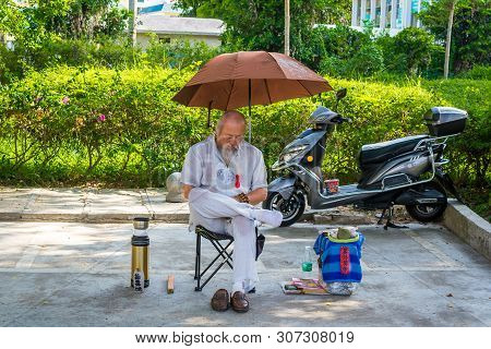 Sanya, Hainan, China - 16 May: 2019: On A Sunny Hot Day, An Unfamiliar Chinese In The Street Sits Un