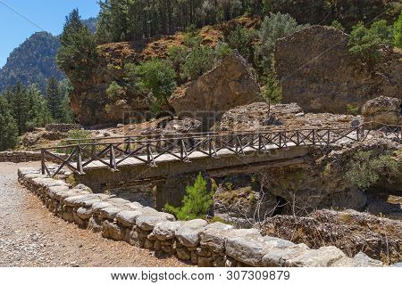 Small Bridge Across River In Old Abandoned Village Of Rumeli On Island Of Crete. Path Through The Sa