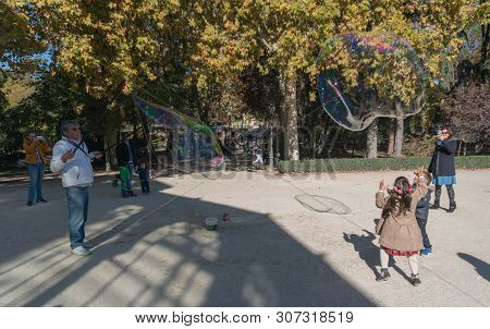 Madrid, Spain - November 12,2017 : Young Unidentified Children Play With Bubbles In Retiro Park Madr