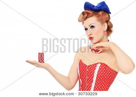 Young beautiful promo pin-up girl in vintage polka dot corset with red dice in hand over white background, copy space