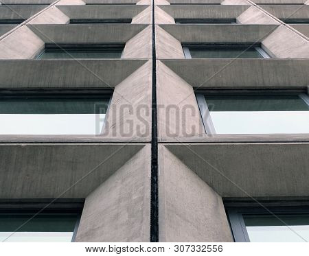 perspective view of geometric angular concrete windows on the facade of a modernist 1960s brutalist style building poster