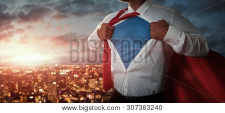 Young Businessman Acting Like A Superhero And Tearing His Shirt Off Over The City At The Sunset With
