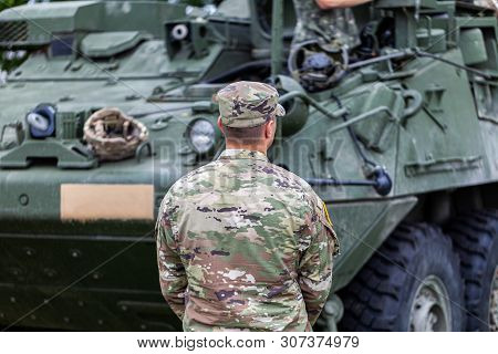 A Soldier From The United States Army Stands In Front Of An Armored Fighting Vehicle
