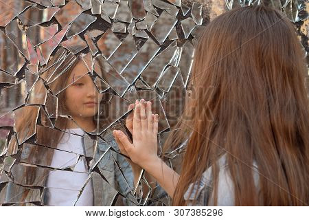 Young Girl Looks In A Broken Mirror And Shows Her Hand On A Mirror