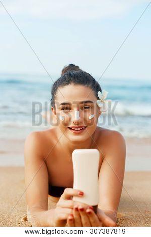 Sunscreen Woman Applying Suntan Lotion Showing Bottle. Beautiful Smiling Happy Woman With Suntan Cre