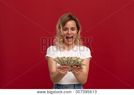 Portrait Of A Girl With Curly Blond Hair Dressed In A White T-shirt Standing On A Red Background. Ha