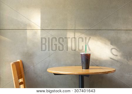 Take Away Plastic Cup Of Iced Black Coffee Americano On Wooden Table In The Restuarant