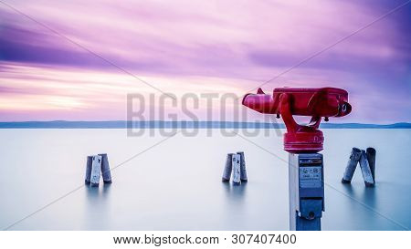 Red Binocular On Sea Shore During One Summer Evening