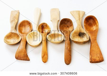 Different Wooden Spoons Are On White Background, Wood Carving And Woodcraft Concept.