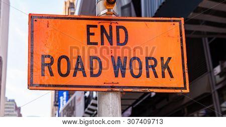 End Road Work. Warning Sign, Orange Color, Blur Buildings Background