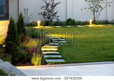 Backyard Of The Mansion With A Flowerbed And A Lawn Of Green Grass With A Marble Walkway Of Square T
