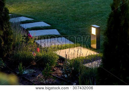 Marble Path Of Square Tiles Illuminated By A Lantern Made Of Metal Glowing With A Warm Light In A Ba