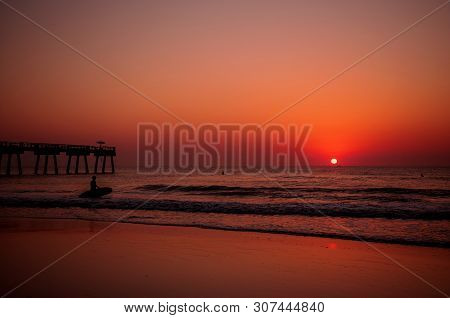 Sunrise On A Beach With Surfers In The Water