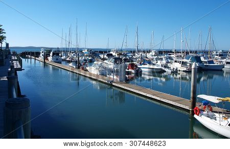 Picturesque Marina. Waterfront Walkway With Boats In Tropical Water With Blue Sky Backdrop. Safe Hav