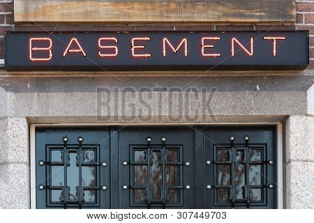 Basement Red Neon Sign Above A Black Door In Daylight