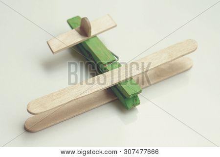 Child artwork, popsicle stick made plane on plain background.