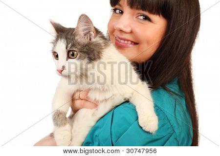 Smiling young woman holds cat isolated on white background; focus on cat