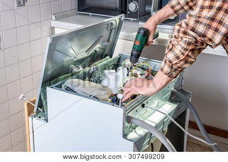 People In Technician Jobs. Appliance Repair Technician Or Handyman Works On Broken Dishwasher In A K