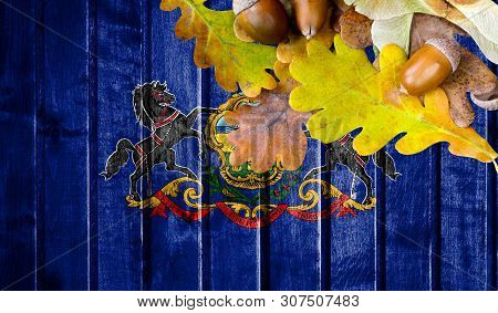 State Of Pennsylvania Flag On Autumn Wooden Background With Leaves And Good Place For Your Text.