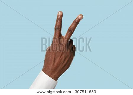 Male Hand In White Shirt Demonstrating A Gesture Of Peace And Friendship Isolated On Blue Studio Bac