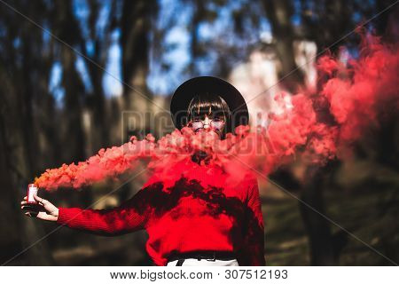 Young Pretty Woman Holding Red Colorful Smoke Bomb On The Outdoor Park. Red Smoke Spreading In The C