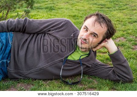 Brunet man in casual clothing relaxing on grass in a park. Daydreaming concept. poster