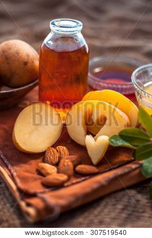 Glowing Face Mask Of Potato Juice In A Glass Bowl On Brown Colored Surface Along With Some Potato Ju
