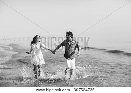 Happy couple walking and playing on the beach, soaking his feet in the water. Wonderful love story in Rimini, Italy. Black and white poster