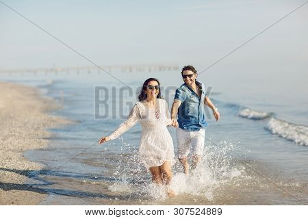 Happy couple walking and playing on the beach, soaking his feet in the water. Wonderful love story in Rimini, Italy poster