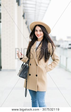 Charming Young Woman In Coat With Long Brunette Hair Wearing A Hat In Big City. Cheerful Emotions, S