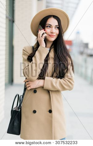 Beautiful Caucasian Woman With Long Dark Hair Talking By Phone With Friend While Standing On Sunny S