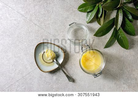 Homemade Melted Ghee Clarified Butter In Open Glass Jar And Spoon On Saucer Over Grey Texture Backgr
