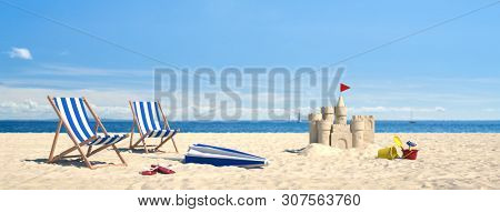 Couple beach chairs lying on the beach with castle in the sand and sea in the background (3d rendering)