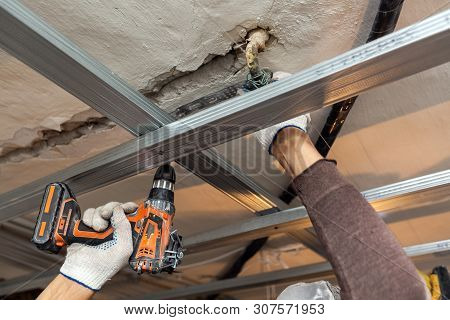 Worker With Protective Gloves Is Drilling By Perforator The Ceiling For Installing Metall Frames  In