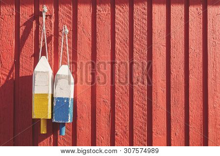 Fishing buoys, used to mark where the lobster pots are dropped, hanging on a red wooden wall in Prince Edward Island, Canada. Spcae for your text.