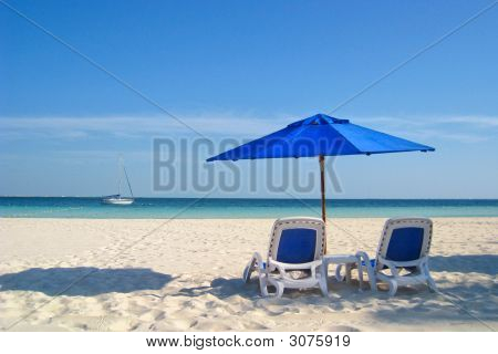 Beach Chairs And Umbrella By The Sea