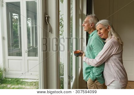 Side view of active senior Caucasian woman embracing senior man near door at home