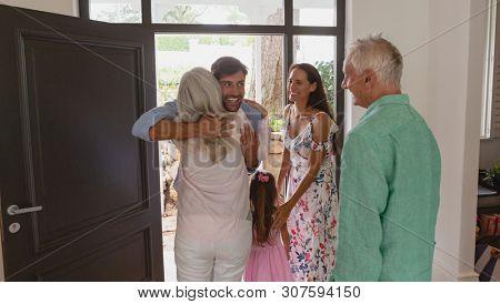 Rear view of happy active senior Caucasian woman embracing  Caucasian man at door in a comfortable home