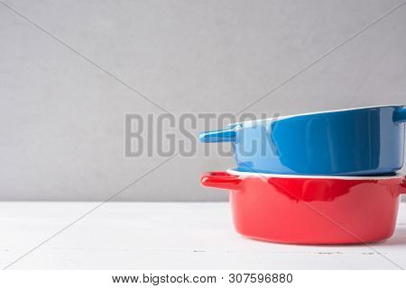 Stack Of Multicolored Red And Blue Ceramic Cooking Pots On White Wood Table Gray Wall Background. Ba