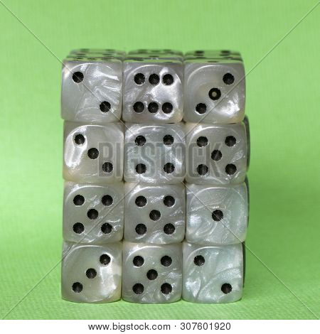A Stack Of Dice Used For Gambling With A Green Background.