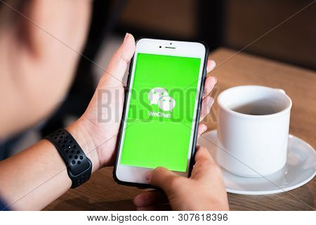 Chiang Mai / Thailand - June 22 2019 : Hands Holding Mobile With Wechat Screen In Coffee Shop.
