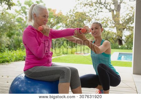 Side view of beautiful Caucasian female trainer assisting active senior Caucasian woman to exercise with dumbbells in the porch