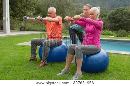 Side view of Caucasian female trainer assisting active senior Caucasian couple to exercise with dumbbells in the backyard