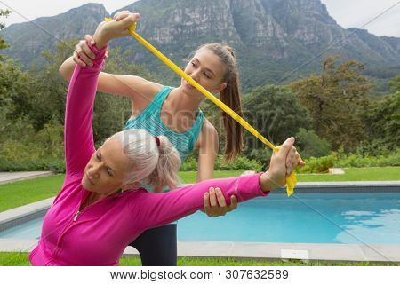 Front view of Caucasian female trainer assisting active senior Caucasian woman to exercise with resistance band in the backyard