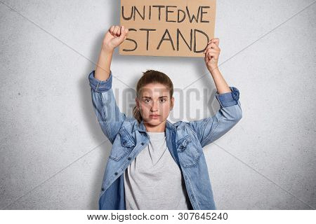 Portrait of militant powerful young feminist showing her fist, holding sign with inscription united we stand in one hand, having decisive facial expression, interested in women social problems. poster